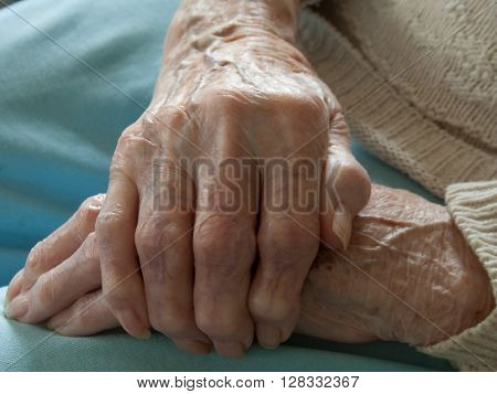 Close-up of woman gripping hand having arthritis