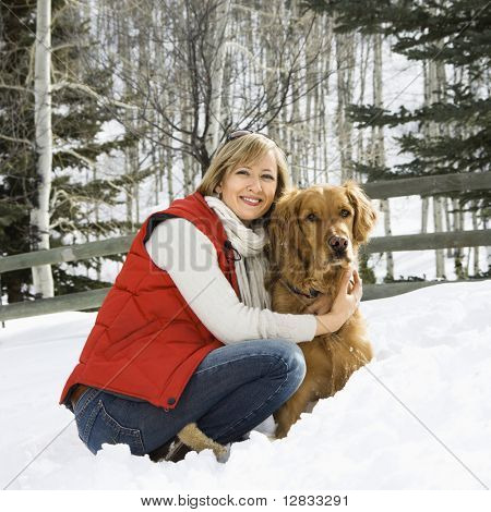 Attractive smiling mid adult Caucasian blond woman squatting in snow with arms around Golden Retriever.