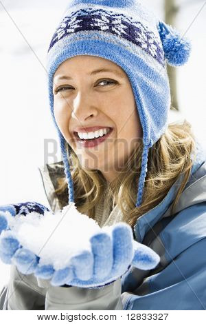 Portrait of attractive smiling mid adult Caucasian blond woman wearing blue ski cap and gloves holding snow towards viewer.