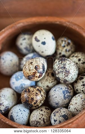 Fresh chicken eggs and quail eggs at wooden plate closeup