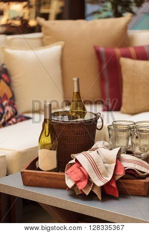 Ice bucket, bottle of white wine, red and white napkins, wine glasses on tray on a rustic patio table in summer.