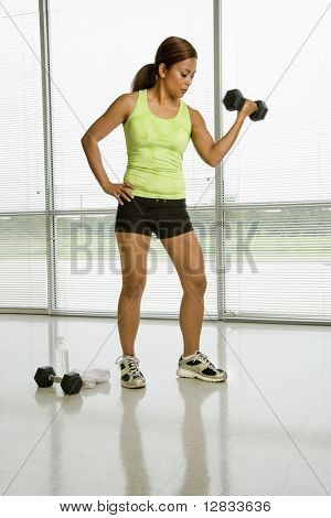 Mid adult Asian woman lifting dumbell with hand on hip.