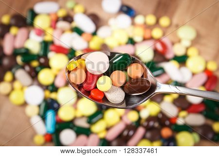 Colorful medical pills on teaspoon and capsules or supplements for therapy in background concept of treatment and health care
