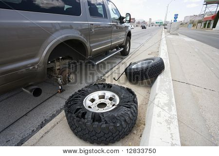 Vehicle brokendown along roadside with damaged tire needing replacement.