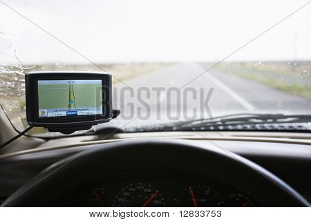 Vehicle dashboard with GPS and view through windshield of highway ahead.