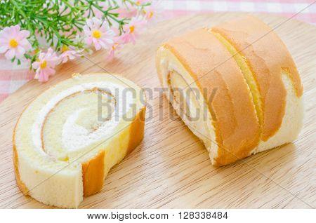 The sweet sponge roll dessert on tablecloth.