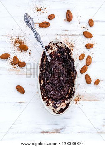 Melted Chocolate With Metal Spoon In Ceramic Bowl And Roast Cocoa Beans  On White Table.