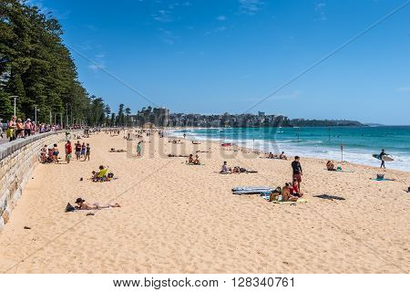 Sydney Australia - November 9 2014: Manly Beach on a sunny sunday morning with tourists and sightseers enjoying the water Sydney Australia. People having fun on Manly beach.