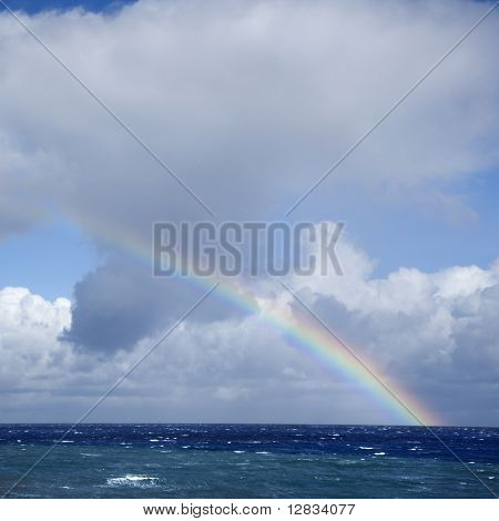 Seascape of the Pacific Ocean near Maui, Hawaii with rainbow and clouds.
