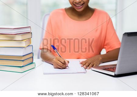 people, technology, learning and education concept - close up of happy african american young woman sitting at table with laptop computer and books and writing to notebook at home