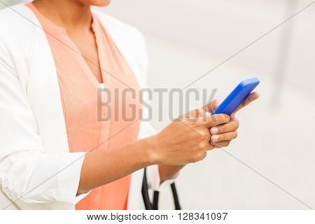 business, technology, communication and people concept - close up of young smiling african american businesswoman texting on smartphone in city