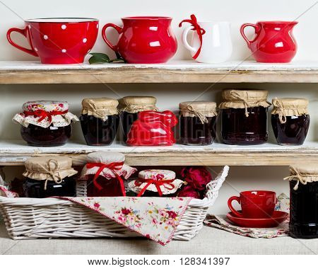 A rustic style. Ceramic tableware and kitchenware in red on the shelves.