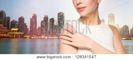 glamour, beauty, jewelry and luxury concept - close up of beautiful woman with golden ring and diamond earring over singapore city skyscrapers background