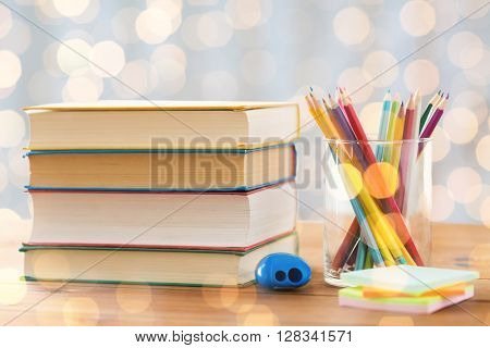 education, school, creativity and object concept - close up of crayons or color pencils with books, stickers and sharpener on wooden table over holidays lights background