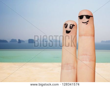 family, couple, travel, tourism and body parts concept - close up of two fingers with smiley faces over beach or infinity edge pool background