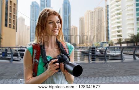 adventure, travel, tourism, hike and people concept - happy young woman with backpack and camera photographing over dubai city and harbor with boats background