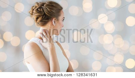 glamour, beauty, jewelry and luxury concept - close up of beautiful woman with golden ring and diamond earring over holidays lights background