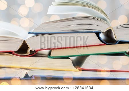 education, school, literature, reading and knowledge concept - close up of books on wooden table over holidays lights background