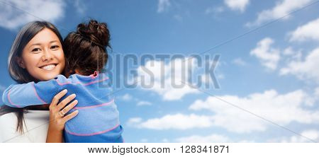 family, children and people concept - happy hugging mother and daughter over blue sky and clouds background