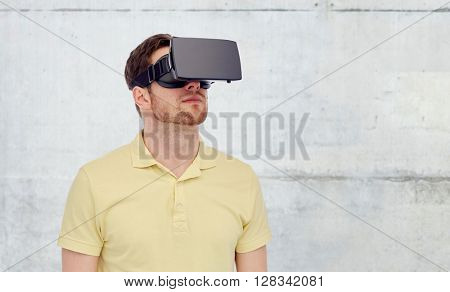 3d technology, virtual reality, entertainment and people concept - young man with virtual reality headset or 3d glasses over concrete gray wall background