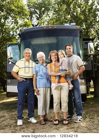 Portrait of three generation Caucasian family standing in front of recreational vehicle smiling and looking at viewer.