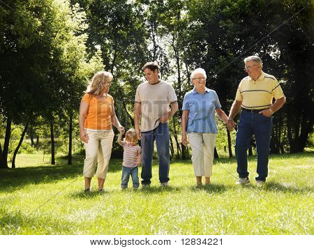 Three generation Caucasian family holding hands walking across grass in park smiling.
