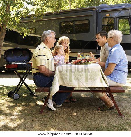 Drei Generation Kaukasische Familie sitzen an Picknicktisch vor Freizeitfahrzeug zu sprechen.