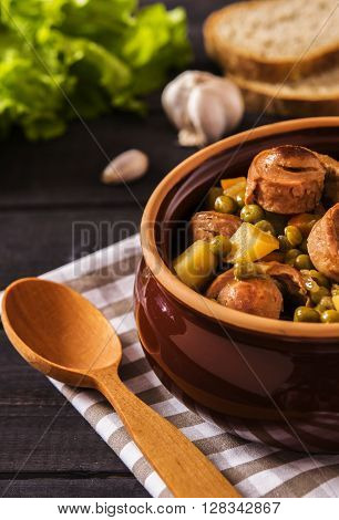 Vegetable stew with pork sausages on dark beer in ceramic bowl on a dark wooden background with garlic, herbs and bread