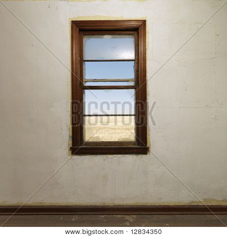 Empty abandoned room with widow centered on wall.