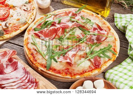 Pizza with prosciutto and mozzarella and with tomatoes and mushrooms on wooden table