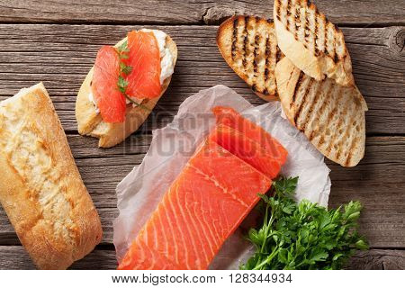 Toast sandwich with ciabatta bread, salmon and cheese on wooden table. Top view