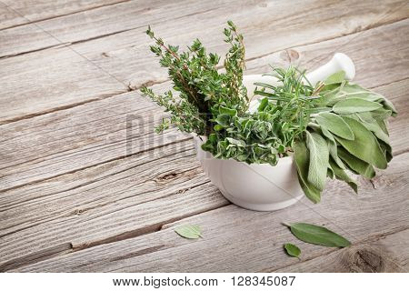 Fresh garden herbs in mortar on wooden table. Oregano, thyme, sage, rosemary. View with copy space
