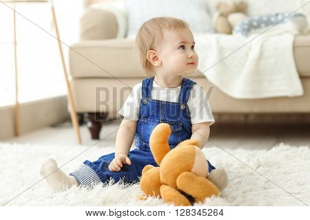 Baby playing with a toy bear on the floor