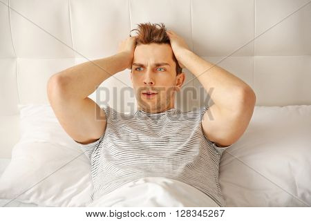 Scared man holding his head while lying in bed.