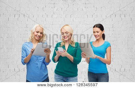 people, technology, communication and leisure concept - happy women with smartphone and tablet pc computers over gray brick wall background