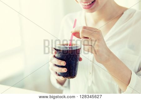 drinks, people and lifestyle concept - close up of happy woman drinking cola from plastic cup with straw at home