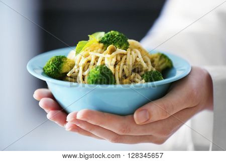Chef hands holding delicious cold pasta salad in bowl closeup