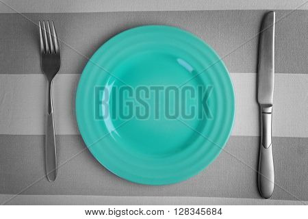 Empty plate with silver fork and knife on striped background