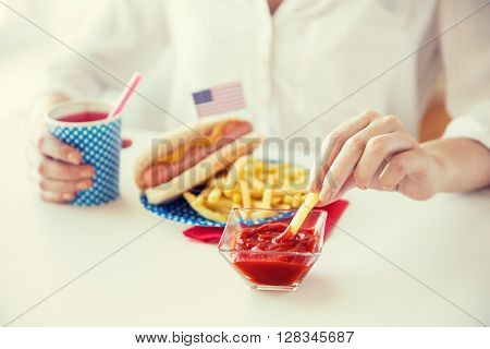 national holidays, celebration, food and patriotism concept - close up of woman eating french fries with hot dog and drinking juice from paper cup at 4th july at party on american independence day