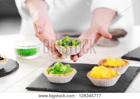 Female hands presenting fresh made fruit tarts.