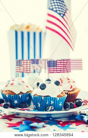 independence day, celebration, patriotism and holidays concept - close up of glazed cupcakes or muffins decorated with american flags and blueberries on plate at 4th july party