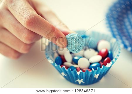 american independence day, celebration, patriotism and holidays concept - close up of female hand taking glazed sweet candies at 4th july theme party