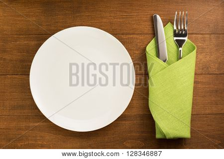 knife and fork with napkin on wooden background