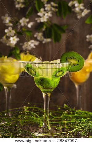 Three cocktails: pineapple, orange, kiwi.  fruit soft drink with ice on a wooden background with flowers.