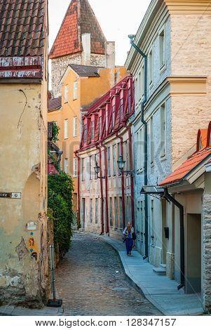 Woman Walking Down The Street Of Old Town Of Tallinn