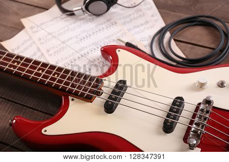 Electric guitar with notes and headphones on wooden background