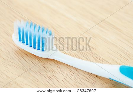 Close up blue color toothbrush on wooden background.