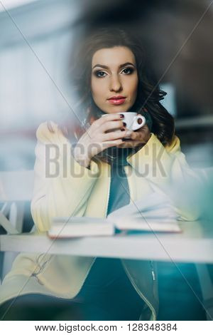 Beautiful young woman with a cup of tea or coffee at a cafe, Beauty Model Woman with the Cup of Hot Beverage. Warm Colors Toned, pretty young woman sitting in the cafe with a cup of tea and a book