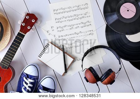 Musical accessories with sunglasses, hat and gumshoes on wooden surface, top view