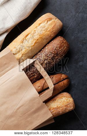 Mixed breads in paper bag on stone table. Top view